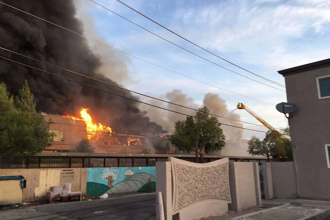 Humo denso y llamas se originan de un incendio en un complejo comercial cerca de Paradise Road ...
