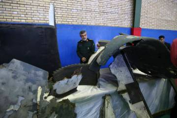 Head of the Revolutionary Guard's aerospace division Gen. Amir Ali Hajizadeh looks at debris fr ...