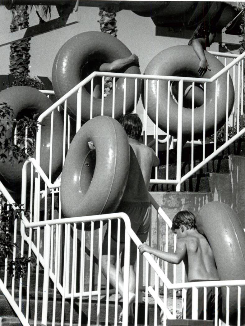 Los invitados llevan salvavidas a la cima de un tobogán en Wet'n'Wild en Las Vegas Boulevard. ...