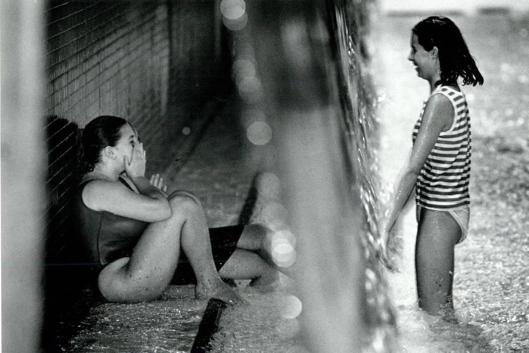 Amigos hablan entre ellos a través de una cascada en Wet'n'Wild en Las Vegas Boulevard durante ...