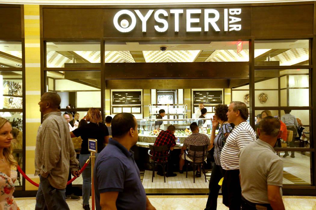 Los huéspedes pasan por el Oyster Bar el día de la inauguración del puerto del de Encore Bos ...