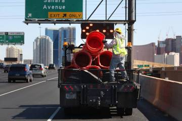 Cuadrillas trabajan para retirar los barriles de seguridad anaranjados a lo largo de la Interes ...