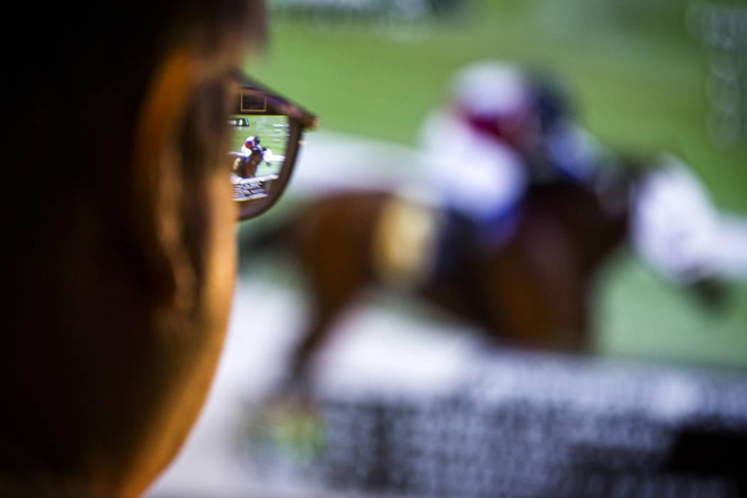 Un hombre ve una carrera de caballos en un monitor de televisión en el William Hill Race & Spo ...