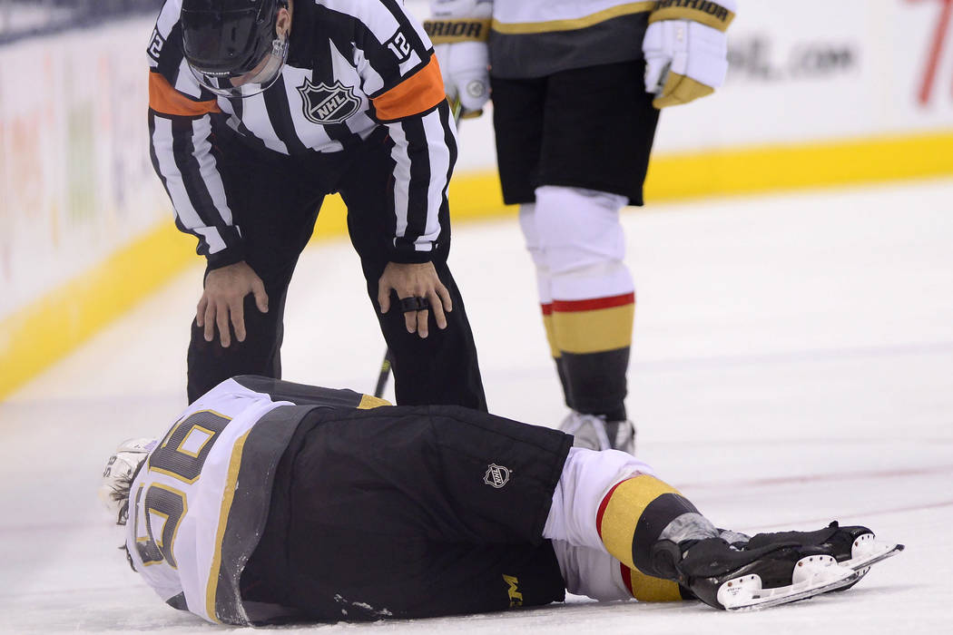 El centro de los Golden Knights de Las Vegas, Erik Haula (56), yace en el hielo después de rec ...