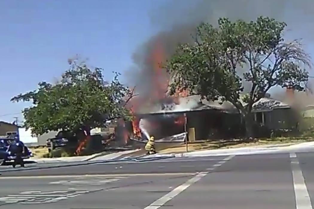 En una imagen tomada de un video, un bombero trabaja para extinguir un incendio en una casa el ...