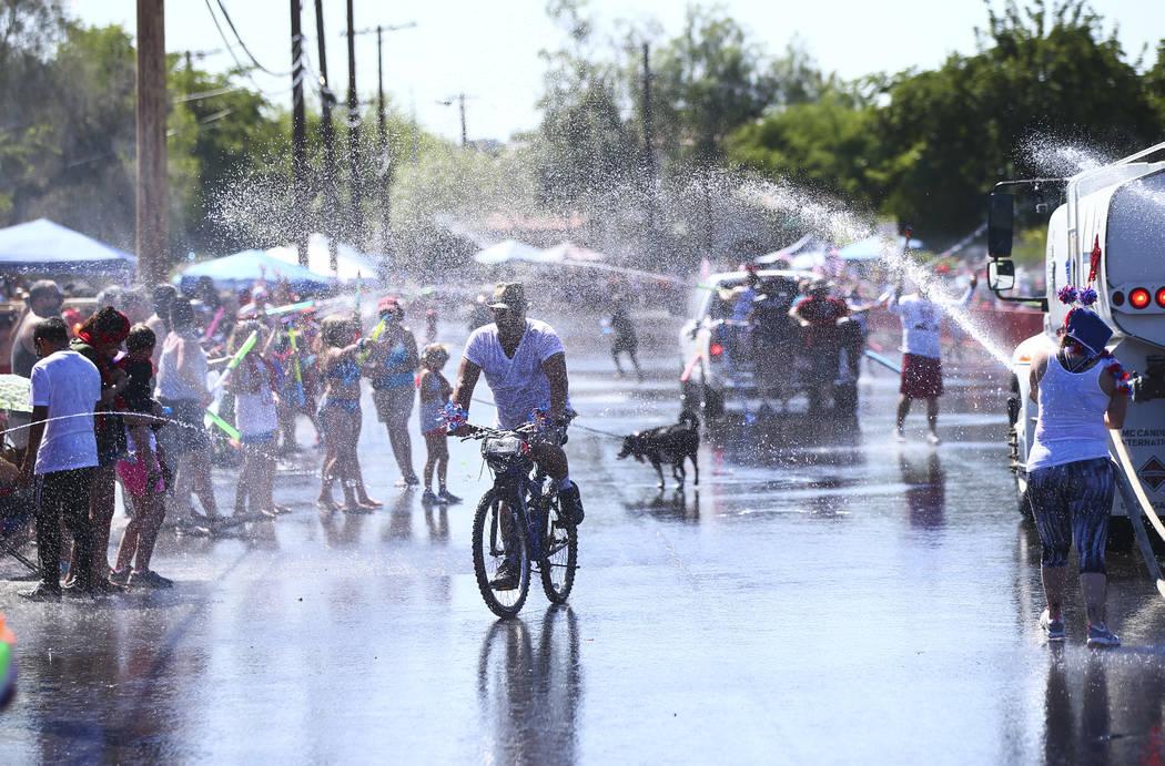 Un hombre monta su bicicleta mientras los espectadores y los participantes del desfile se rocí ...