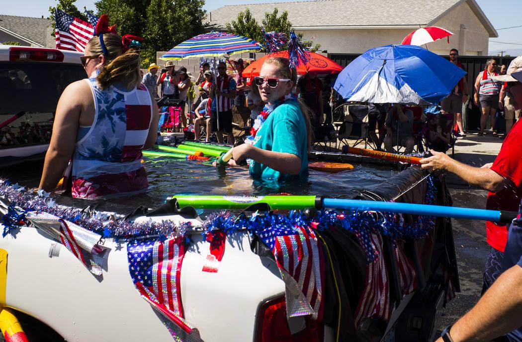 Los participantes del desfile se preparan para participar en las peleas de agua durante el desf ...