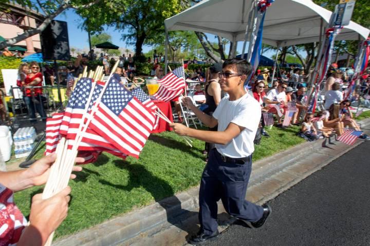 Angel Lemurs, de 16 años, reparte banderas estadounidenses durante el 25º desfile patriótico ...
