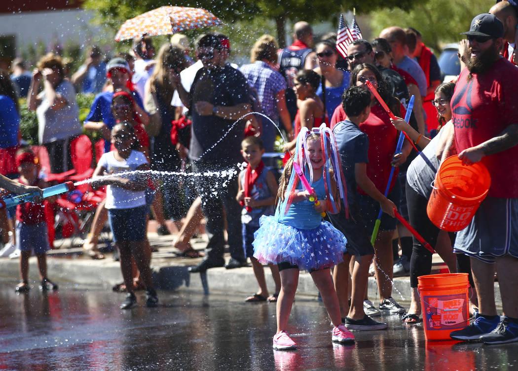 Los espectadores del desfile participan en peleas de agua durante el desfile en la celebración ...