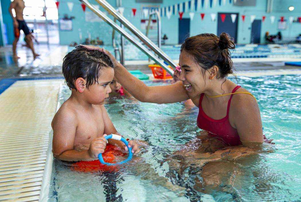 La instructora de natación Shanneal Ocular, habla con su estudiante Louis Borado, de 3 años, ...