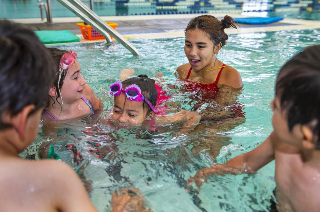 Lorelai Zimring, 5, izquierda, y Ariana Villeda, 4, centro, trabajan con la instructora de nata ...