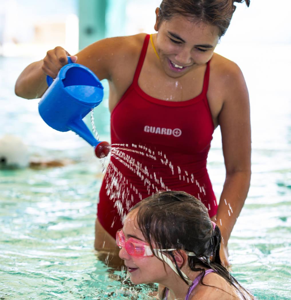 La instructora de natación Shanneal Ocular, arriba, rocía agua sobre la cabeza de su estudian ...