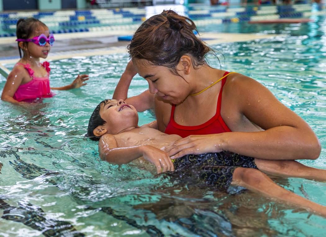 La instructora de natación Shanneal Ocular, derecha, ayuda a su estudiante Stefan Flores, de 4 ...