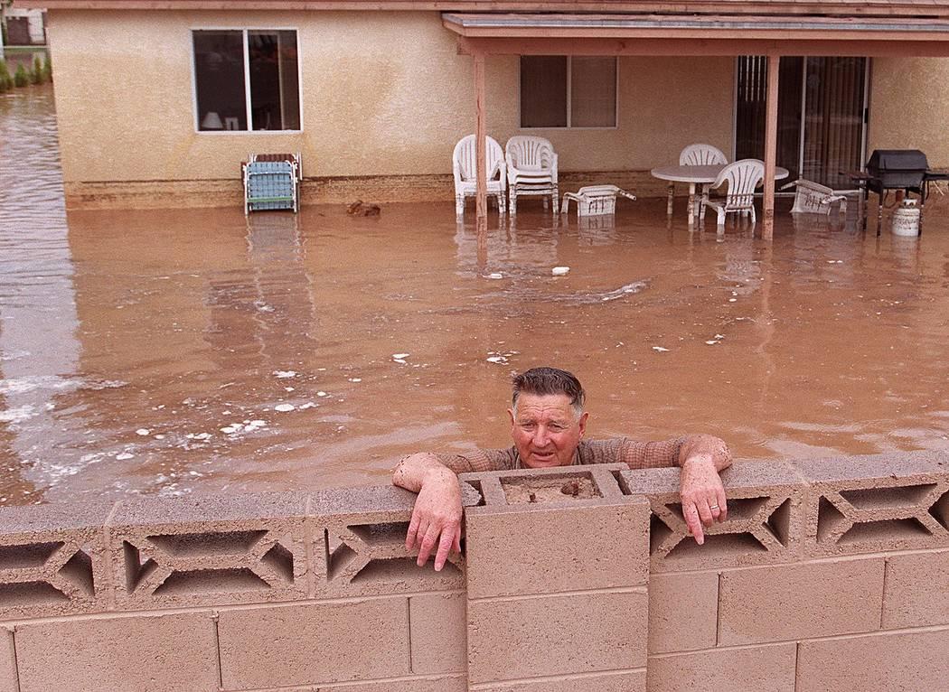 Un hombre se para en el patio trasero de su casa inundada durante la inundación de 1999. (Las ...