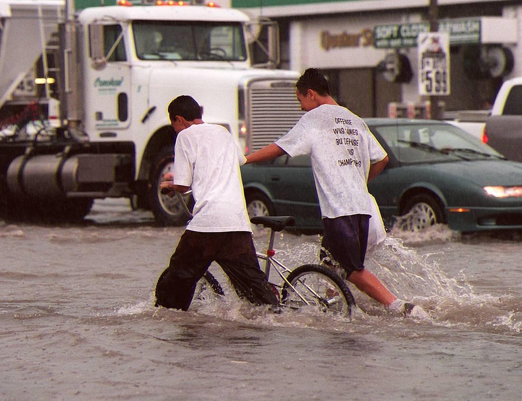 Dos muchachos empujan una bicicleta a través de la intersección de Charleston y Lamb el jueve ...