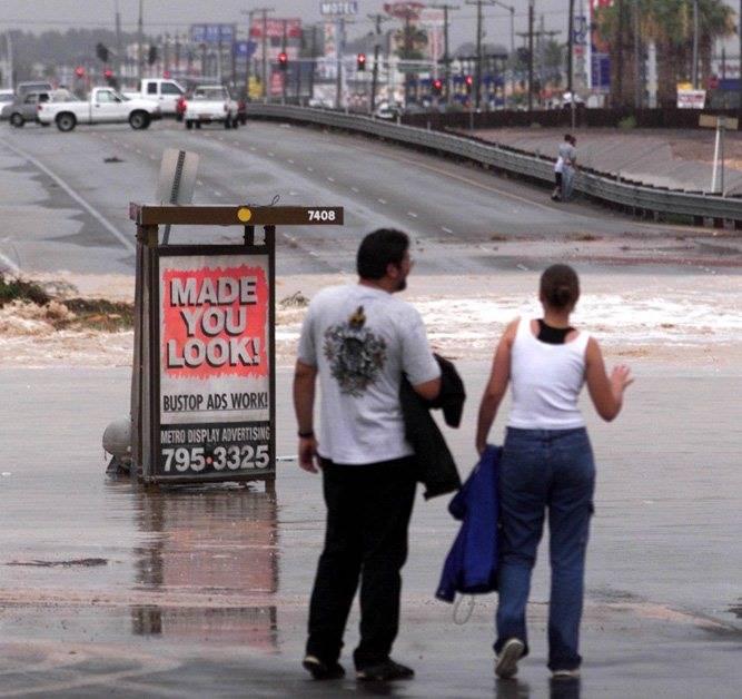Los espectadores observan las inundaciones que cruzan la carretera de Boulder cerca del Sahara. ...