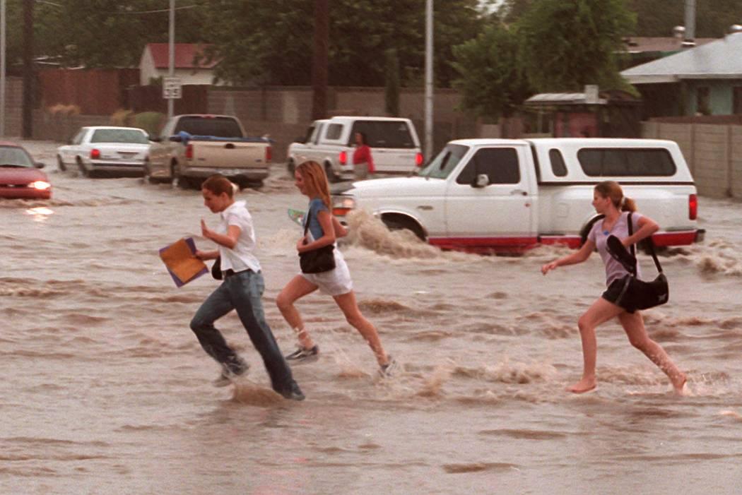 Niños cruzan una calle inundada cerca de Washington y Pecos. (Las Vegas Review-Journal)