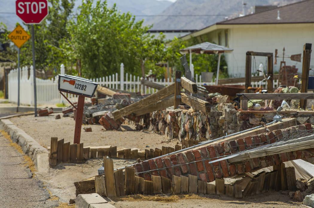 Una pared de ladrillos y madera en frente de una casa es una de las muchas estructuras dañadas ...