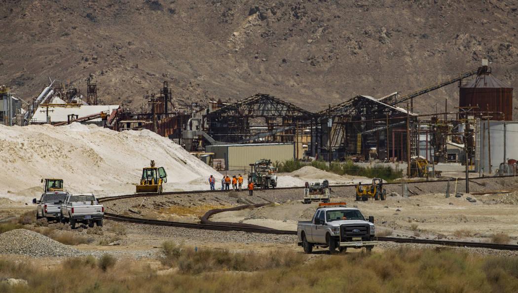 Una cuadrilla de ferrocarriles trabaja para reparar la línea que conduce a la planta de Searle ...