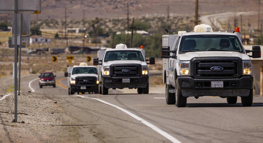Los vehículos de reparación de servicios públicos ingresan a Trona, California, ya que los s ...