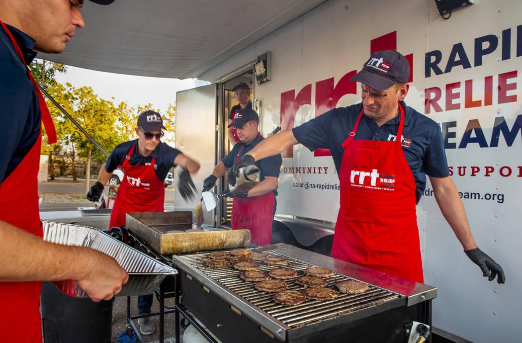 Los miembros de un Equipo de Ayuda Rápida de la Cruz Roja se preparan para servir hamburguesas ...
