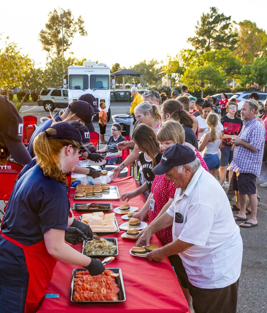 Los miembros de un Equipo de Ayuda Rápida de la Cruz Roja sirven hamburguesas a los clientes e ...
