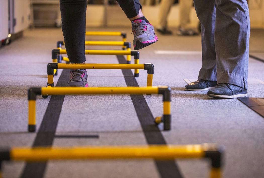 Un paciente pasa por pequeños obstáculos dentro del departamento de fisioterapia de la Clíni ...