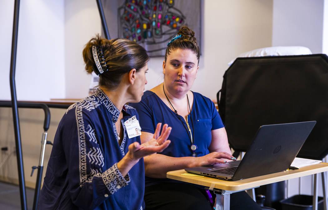 La directora de mercadotecnia y comunicaciones Nicole Wolf consulta con la fisioterapeuta Sondi ...