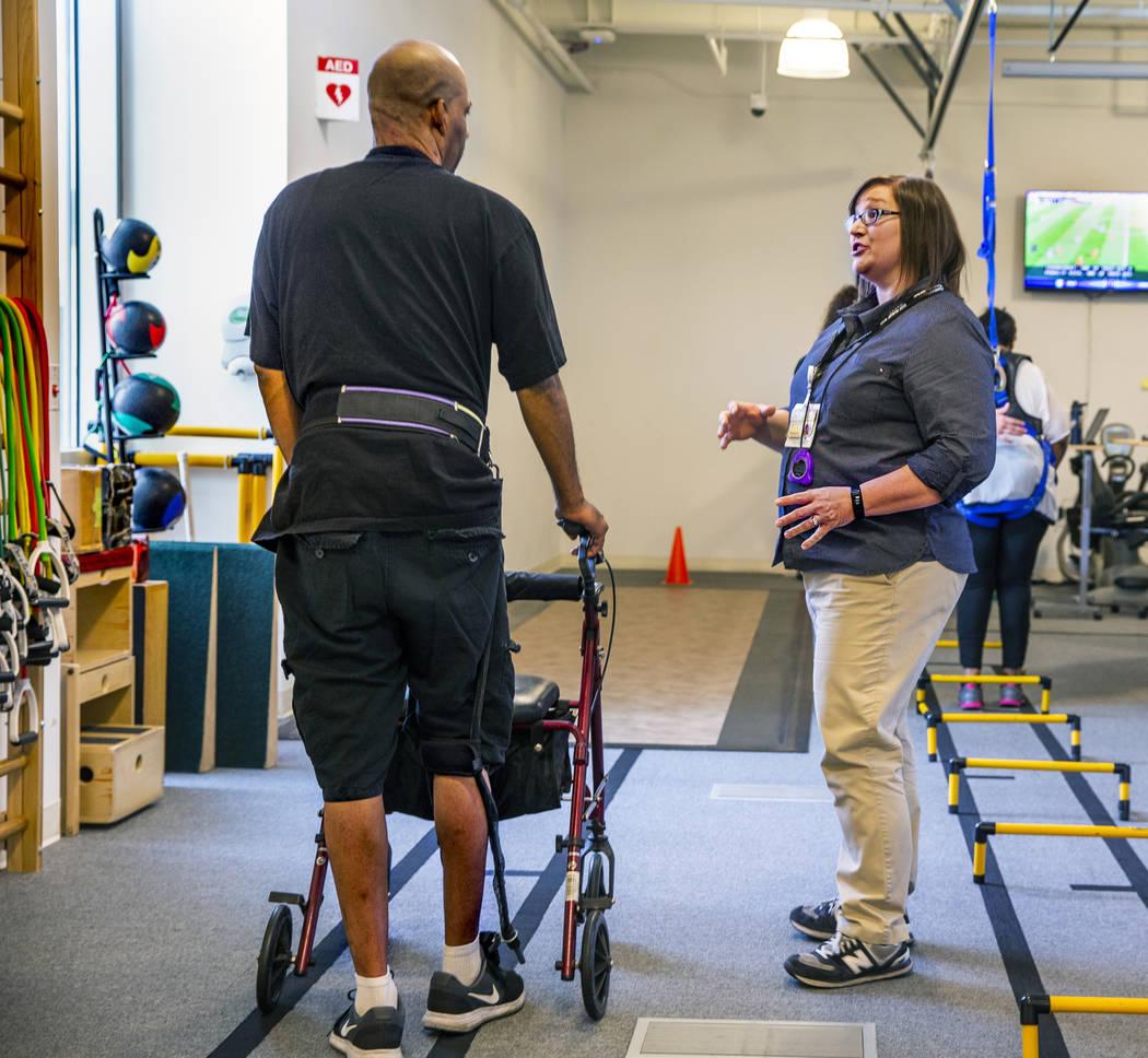 Una paciente consulta a la fisioterapeuta Christine Ross en un ejercicio de caminata en el depa ...