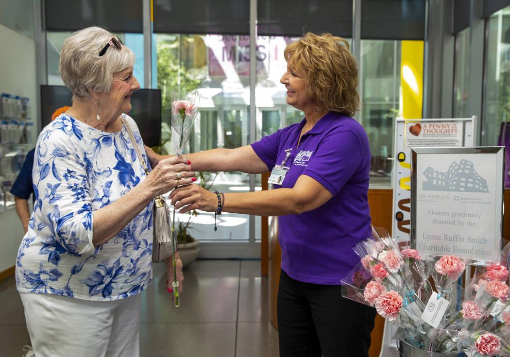 La paciente Ann Ayton recibe una flor de Lisa Naves en la Clínica Cleveland Lou Ruvo Center fo ...