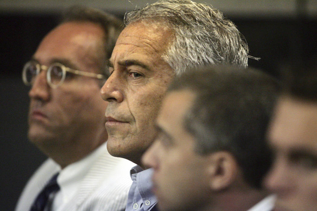 En una foto de archivo del 30 de julio de 2008, Jeffrey Epstein (al centro) se encuentra bajo c ...