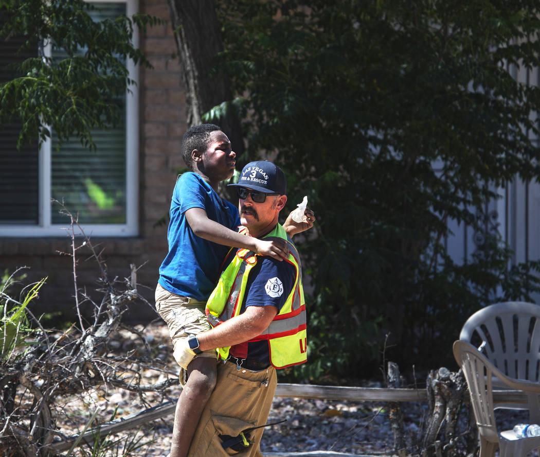 Un bombero carga a uno de los niños heridos en un accidente en West Washington Avenue cerca de ...