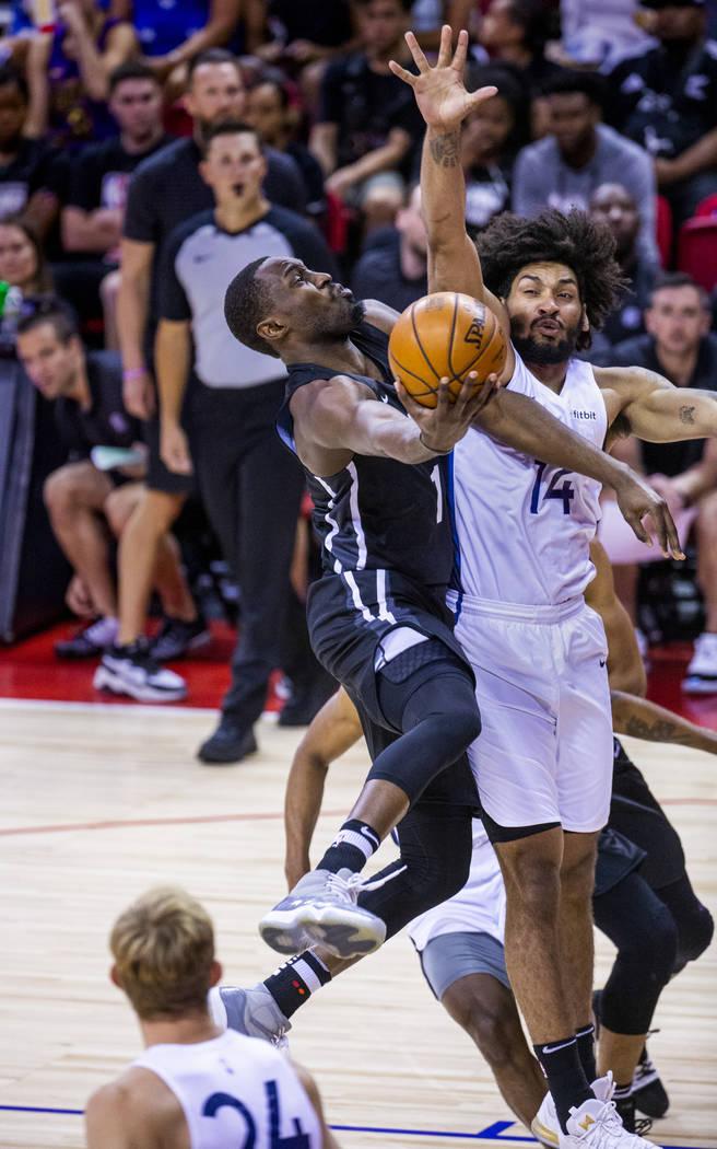 El escolta de los Nets de Brooklyn, Theo Pinson, a la izquierda, eleva y rodea al alero Jordan ...