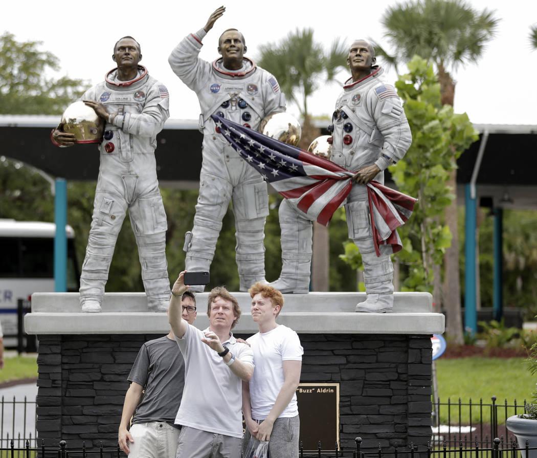Los invitados se toman una foto frente a una nueva estatua de los astronautas del Apolo 11, de ...