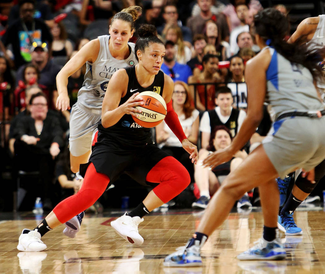 Kayla McBride (21), jugadora de Las Vegas Aces, bota el balón contra Lexie Brown (4), de Minne ...