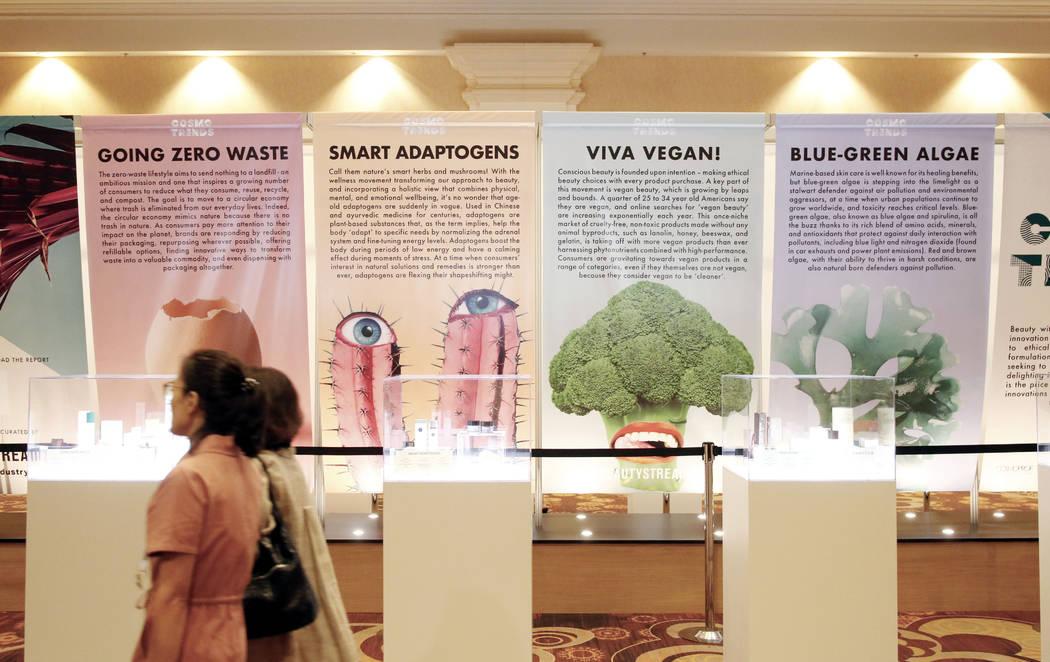 Las personas que caminaron pasaron una pancarta de Cosmo Trends sobre productos éticos, vegano ...