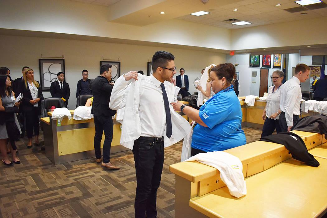 Los estudiantes, como Alexander Makabeh se midió su Bata Blanca, el primer paso físico y simb ...