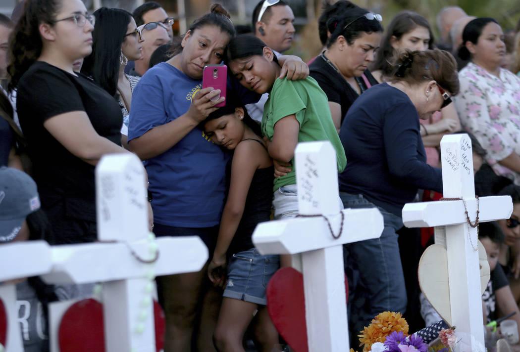 Una madre se aferra a sus hijas mientras visitan un monumento conmemorativo para las víctimas ...