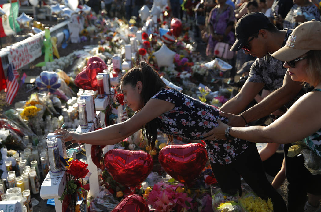 Una mujer se inclina para escribir un mensaje en una cruz de un memorial improvisado en la esce ...