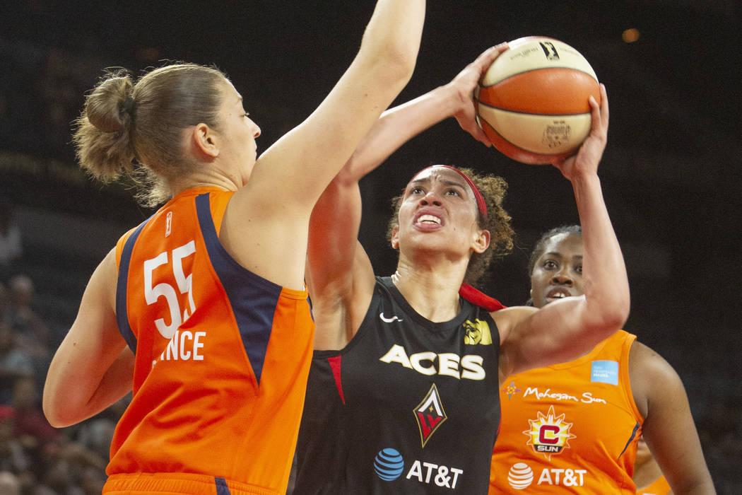 La jugadora de Las Vegas Aces, Dearica Hamby -centro-, va al aro contra su rival de Connecticut ...