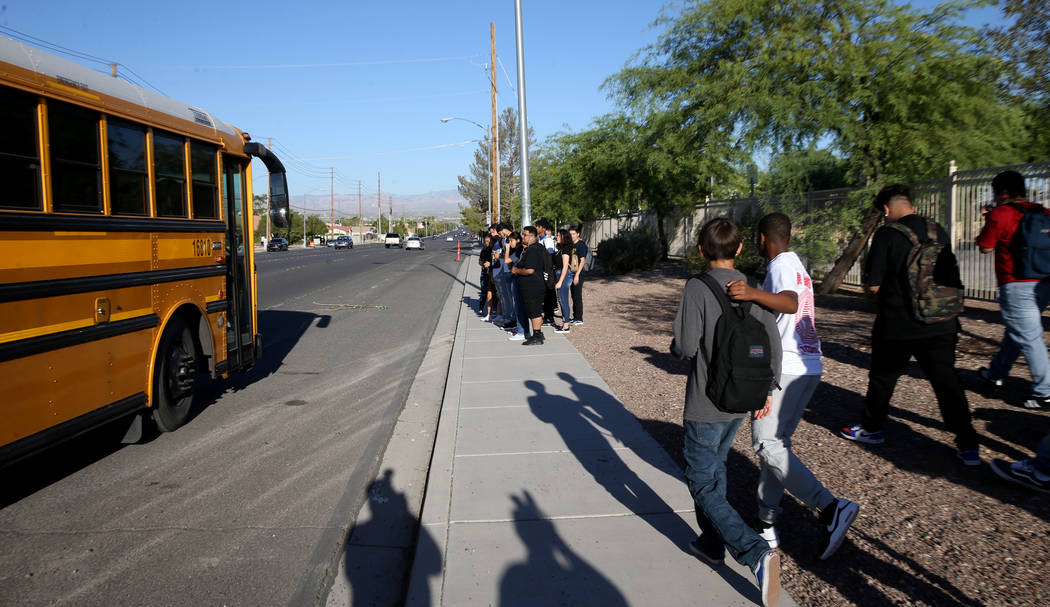 Estudiantes de la Preparatoria Sunrise Mountain se preparan para abordar el autobús escolar en ...