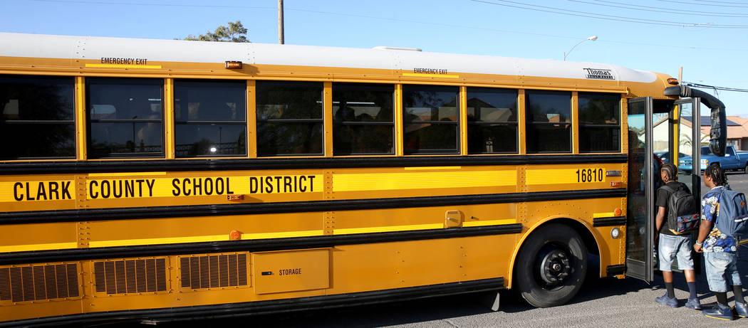 Estudiantes de la preparatoria Sunrise Mountain abordan el autobús escolar en East Owens Avenu ...