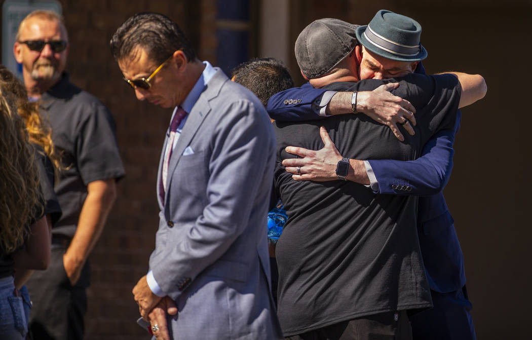 Jason Deborski, de espaldas, recibe un abrazo mientras dolientes se reúnen para el funeral de ...