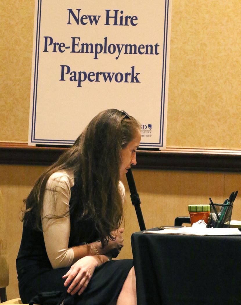 Ashley Robins, revisa documentos durante el evento de contratación de maestros nuevos del Dist ...
