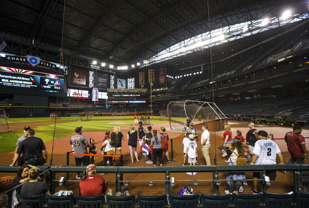 Fans del béisbol con acceso previo ven a los equipos practicar antes de un partido de los Diam ...