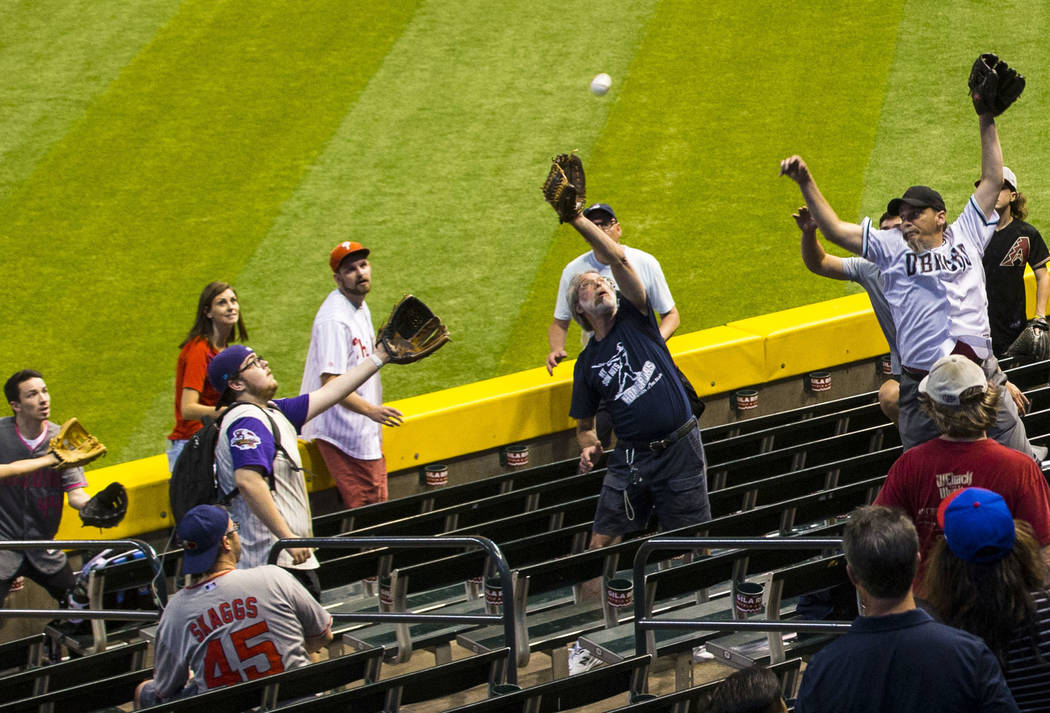 Fans del béisbol saltan por la pelota mientras los equipos practican antes del comienzo de un ...