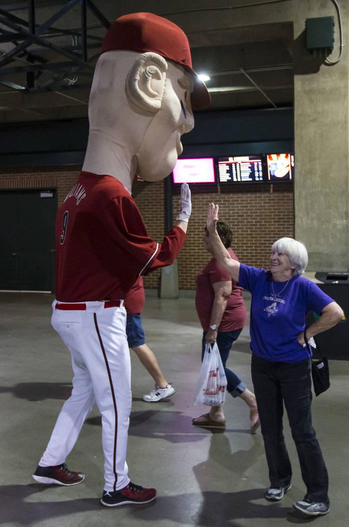 Cindy McBride, de Phoenix, choca los cinco con la mascota de gran tamaño que representa a Matt ...
