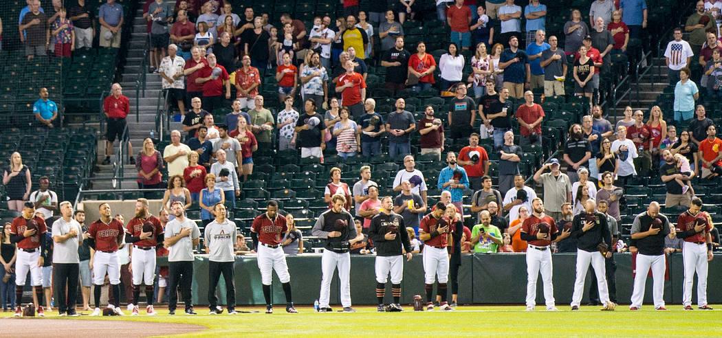 Los miembros de los Diamondbacks de Arizona se paran para cantar el himno nacional antes de jug ...