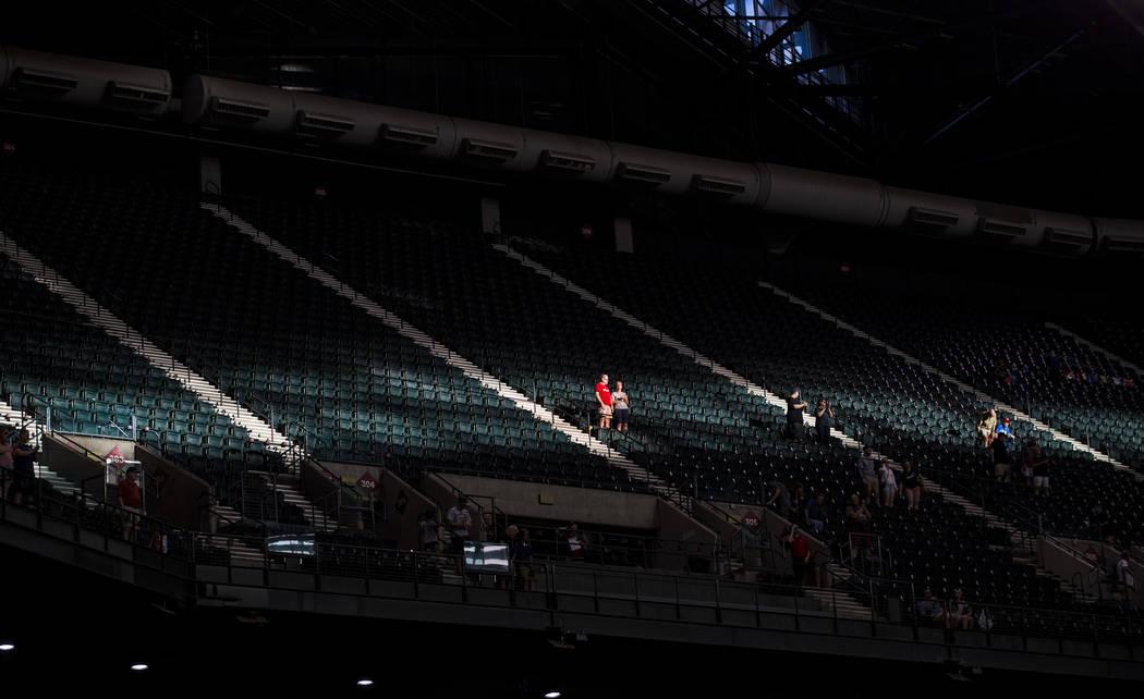 Fans resaltados por una franja de luz solar antes del comienzo de un juego de béisbol de los D ...