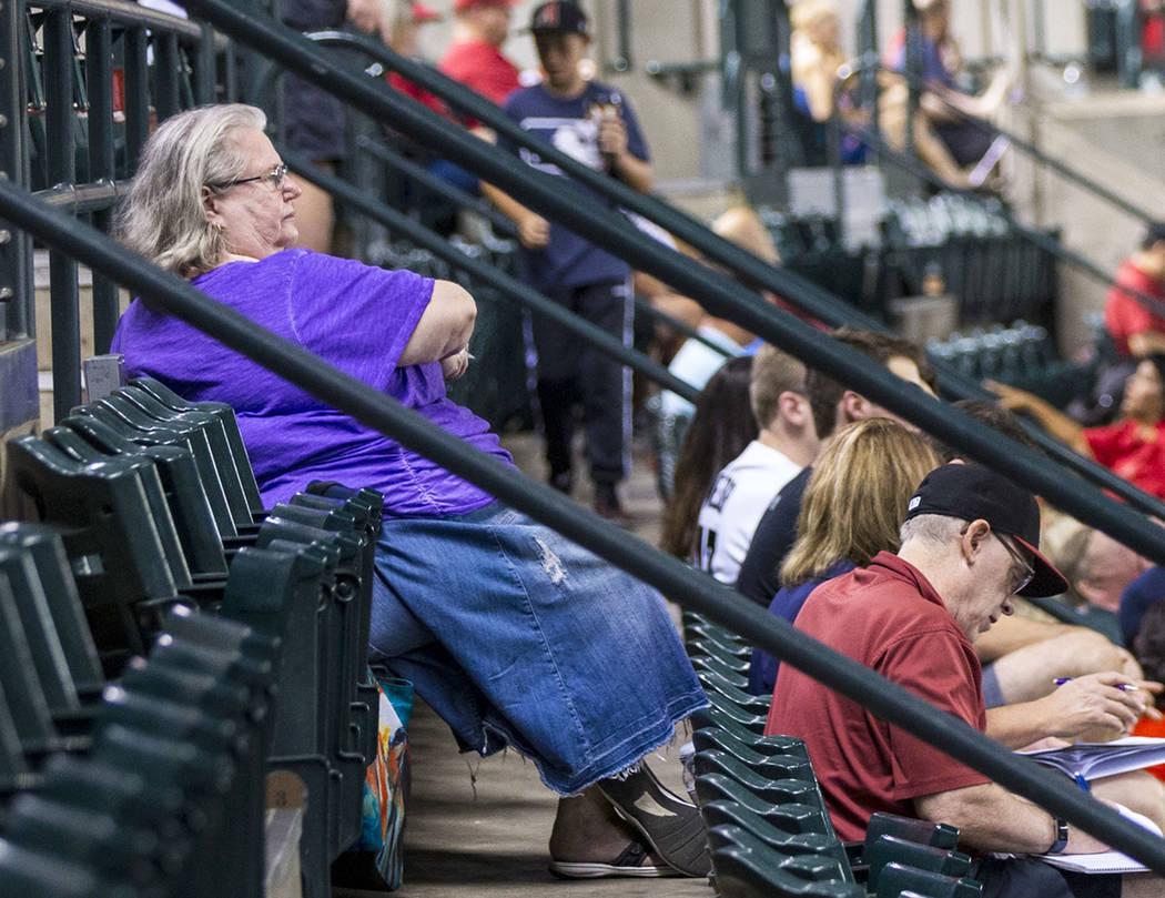 Jackie Laird, de Phoenix, en púrpura, observa la acción de un juego de béisbol de los Diamon ...
